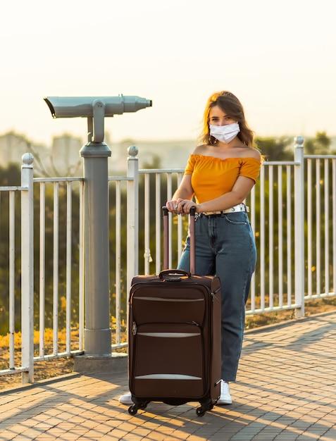 Jonge brunette meisje met chirurgisch masker is poseren met haar koffer in de buurt van een verrekijker in park. Premium Foto