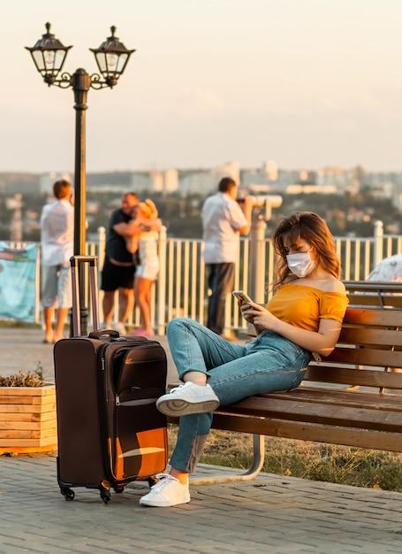 Jonge brunette meisje met een chirurgisch masker browsen door haar telefoon zittend in het park met haar koffer in de buurt van haar. Premium Foto