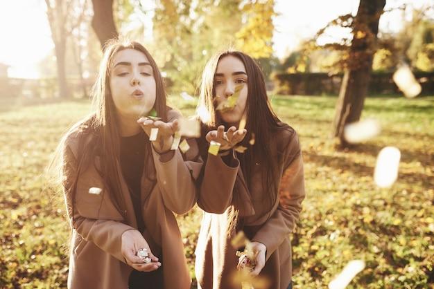 Jonge brunette tweelingzusjes staan dicht bij elkaar en blazen confetti in de camera, met een aantal van die in hun handen, casual jas dragen in herfst zonnig park op onscherpe achtergrond. Premium Foto