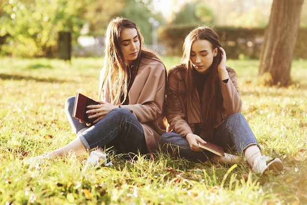 Jonge brunette tweelingzusjes zitten dicht bij elkaar met gesloten ogen op het gras, benen licht gebogen in de knieën en gekruist, met bruine boeken, casual jas dragen in herfst park op achtergrond. Premium Foto