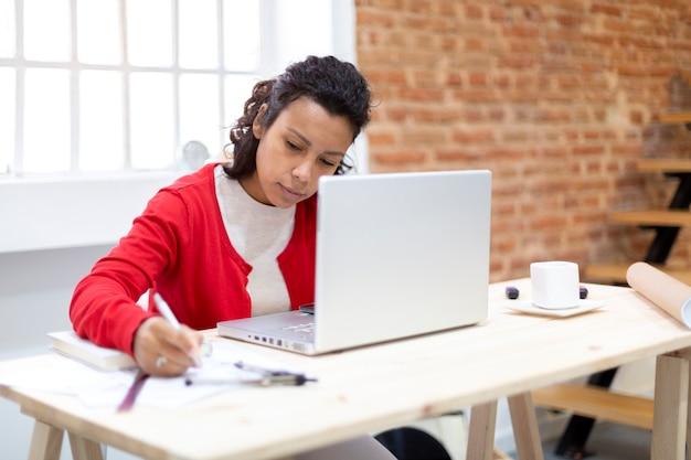 Jonge brunette vrouw hard werken vanuit haar kantoor aan huis. ruimte voor tekst. concept van plannen en nieuwe projecten. Premium Foto