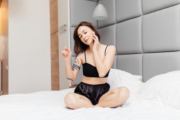 Jonge brunette vrouw in sexy ondergoed luisteren muziek met koptelefoon op het bed Gratis Foto