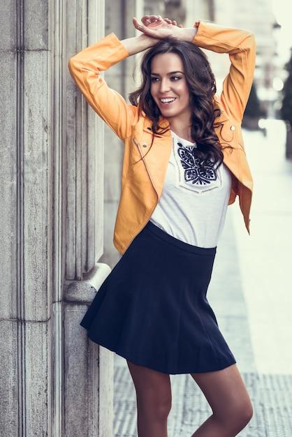 Jonge brunette vrouw lachend in stedelijke achtergrond. Gratis Foto