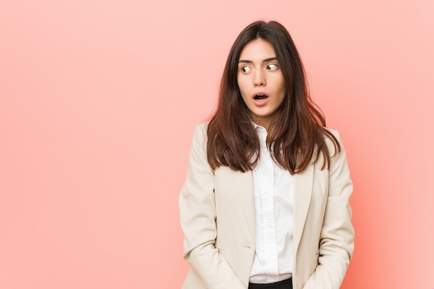 Jonge brunette zakelijke vrouw tegen een roze wordt geschokt omdat ze iets heeft gezien. Premium Foto