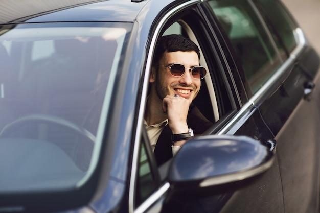 Jonge bussinesman in pak en zwarte bril zijn auto rijden. bussines kijken. proefrit van de nieuwe auto Premium Foto