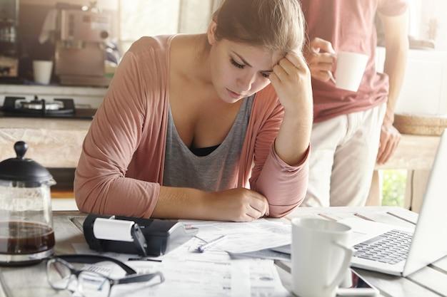 Jonge casual vrouw met depressieve blik tijdens het beheren van de financiën van het gezin en het doen van papierwerk, zittend aan de keukentafel met veel papier, rekenmachine en laptop Gratis Foto