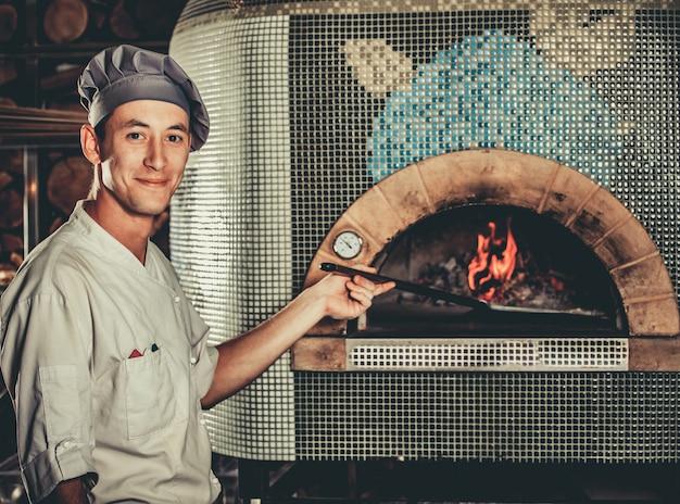 Jonge chef-kok die traditionele italiaanse pizza voorbereidt Premium Foto