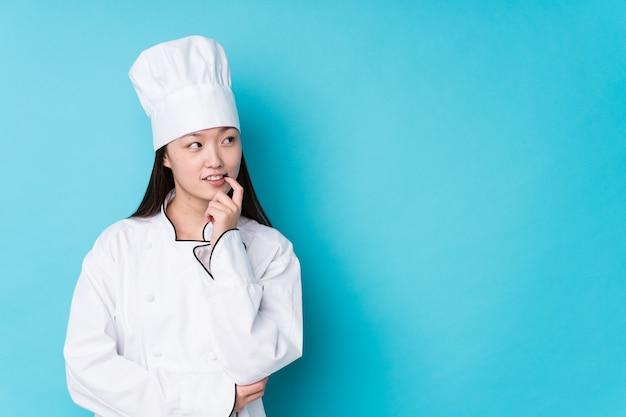 Jonge chinese geïsoleerde chef-kokvrouw ontspannen denkend over iets dat een exemplaarruimte bekijkt. Premium Foto