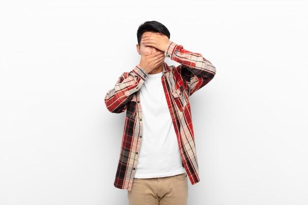 Jonge chinese man die gezicht bedekt met beide handen nee zeggen! afbeeldingen weigeren of foto's verbieden tegen een egale kleurenmuur Premium Foto