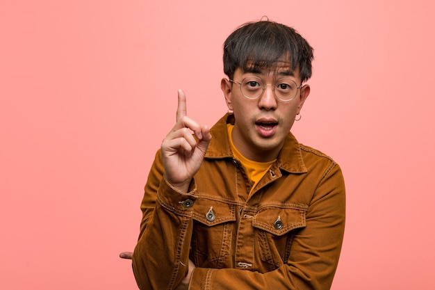 Jonge chinese man met een jasje met een geweldig idee, concept van creativiteit Premium Foto