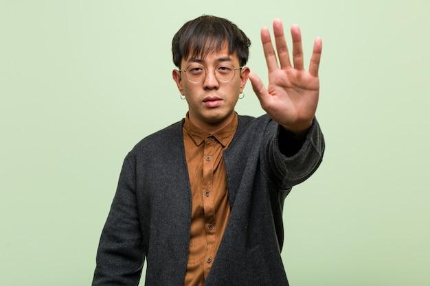 Jonge chinese man tegen een groene muur Premium Foto