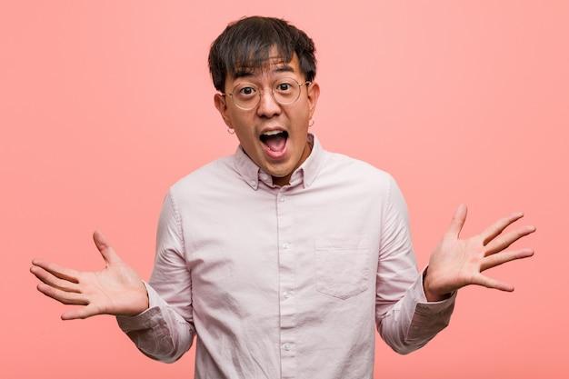 Jonge chinese mens die een overwinning of een succes viert Premium Foto