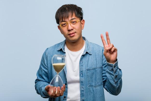Jonge chinese mens die een zandloper houdt die nummer twee toont Premium Foto