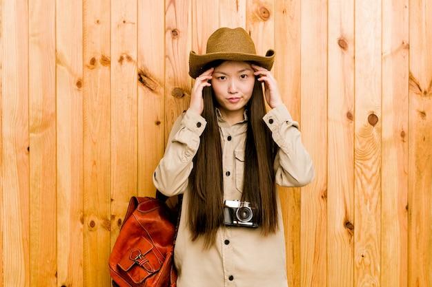 Jonge chinese reizigersvrouw concentreerde zich op een taak, die wijsvingers hoofd houden. Premium Foto