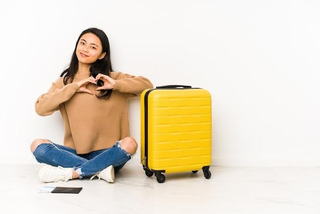 Jonge chinese reizigersvrouw die op de vloer met een geïsoleerde koffer zit die en een hartvorm met handen glimlacht toont. Premium Foto