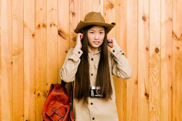 Jonge chinese reizigersvrouw die oren behandelen met handen. Premium Foto