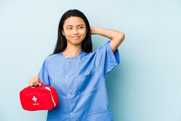 Jonge chinese verpleegstersvrouw die op een blauwe muur wordt geïsoleerd die aan het luisteren van een roddel probeert te luisteren. Premium Foto