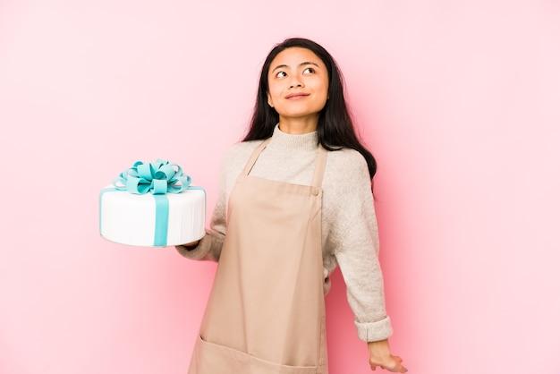 Jonge chinese vrouw die een cake houdt geïsoleerd verrast en geschokt. Premium Foto