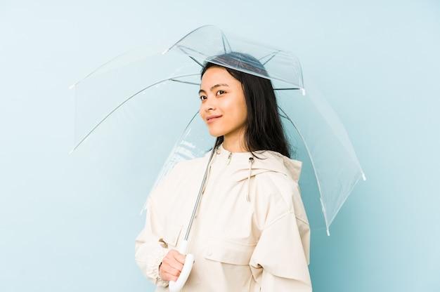 Jonge chinese vrouw die een geïsoleerde paraplu houdt die zijwaarts met twijfelachtige en sceptische uitdrukking kijkt. Premium Foto