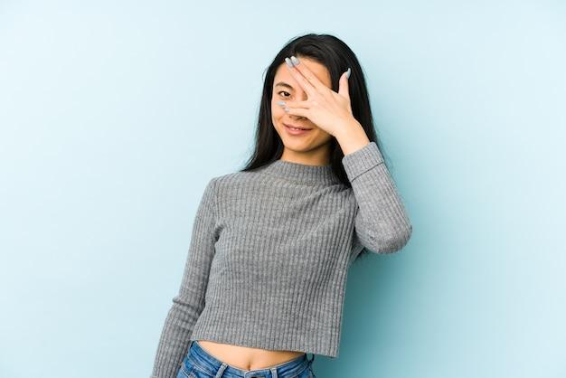 Jonge chinese vrouw knipperen door vingers, beschaamd bedekkend gezicht. Premium Foto