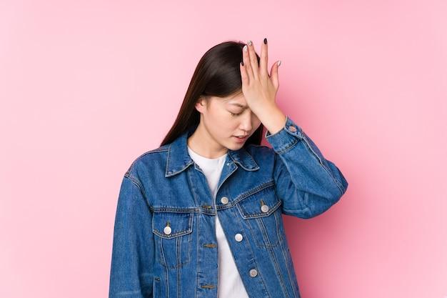 Jonge chinese vrouw poseren op roze geïsoleerd iets vergeten, voorhoofd met palm slaan en ogen sluiten. Premium Foto