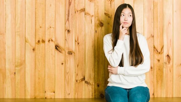 Jonge chinese vrouwenzitting op een houten plaats die zijdelings met twijfelachtige en sceptische uitdrukking kijkt. Premium Foto