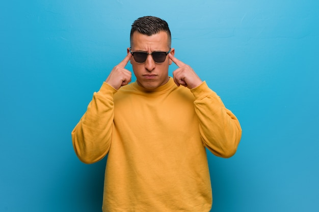 Jonge colombiaanse man doet een concentratie gebaar Premium Foto