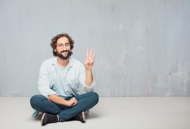 Jonge cool bebaarde man zittend op de vloer. grunge muur achtergrond Premium Foto