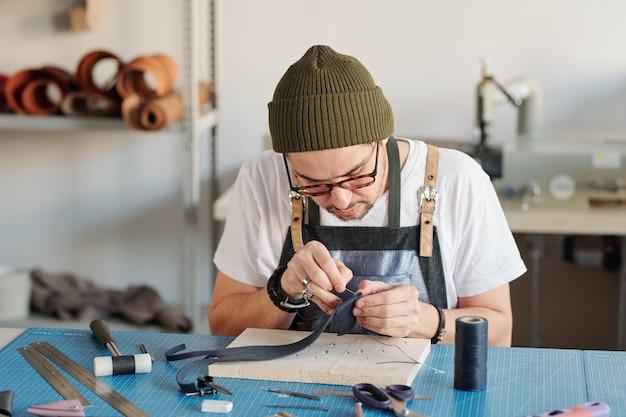 Jonge creatieve leatherworker bukken tafel tijdens het naaien van nieuw zwart leer item over houten plank in werkplaats Premium Foto