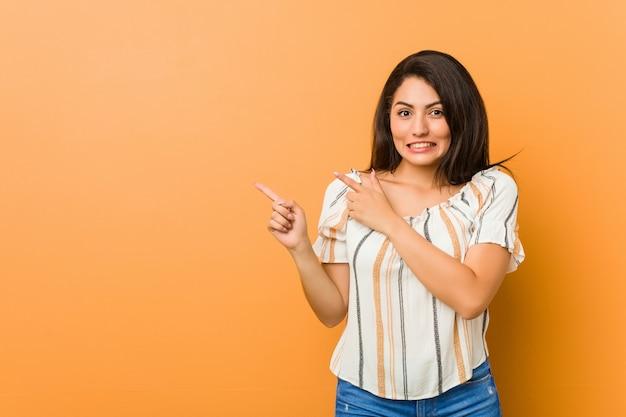 Jonge curvy geschokte vrouw wijzend met wijsvingers aan a. Premium Foto