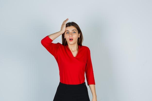 Jonge dame die hand op hoofd in rode blouse, rok houdt en vergeetachtig kijkt Gratis Foto
