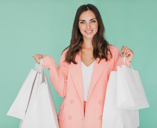 Jonge dame die in roze jasje bij camera glimlacht Gratis Foto