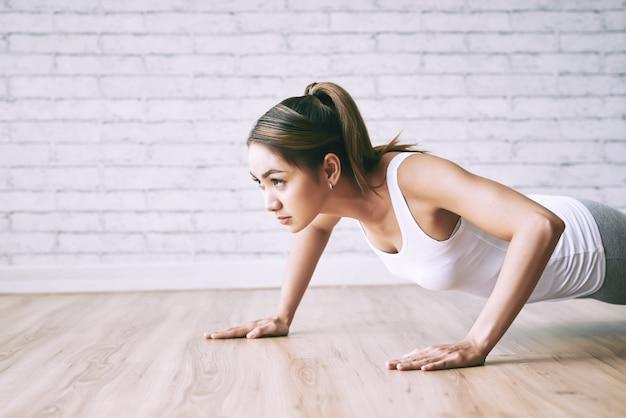 Jonge dame die opdrukoefeningen op de vloer thuis met zolderontwerp doet Gratis Foto
