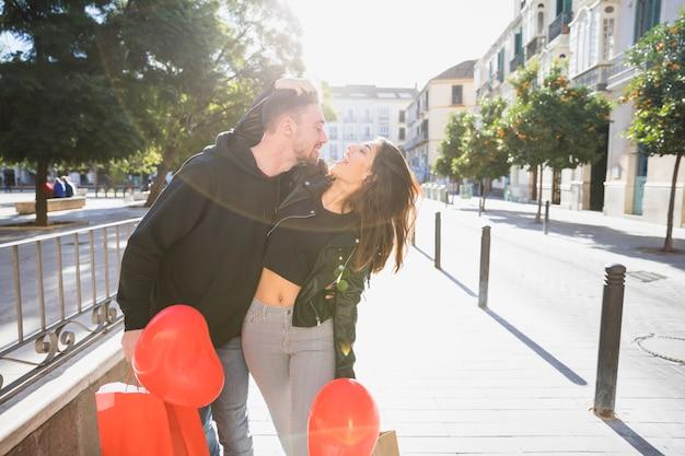 Jonge dame en lachende man met pakketten en ballonnen plezier op straat Gratis Foto
