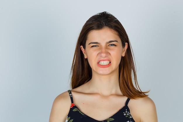 Jonge dame in bloementop die tanden toont en boos kijkt Gratis Foto