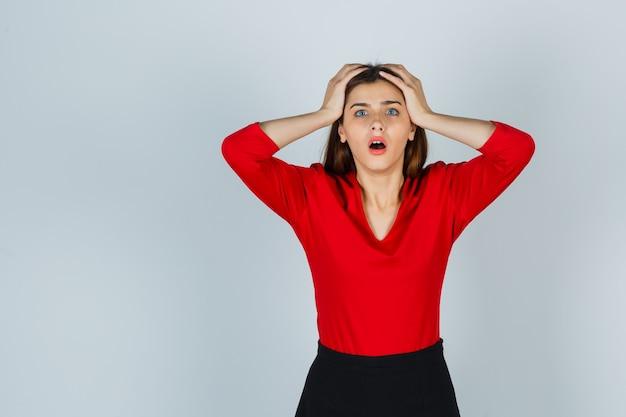 Jonge dame in rode blouse, rok die de handen op hoofd houdt en vergeetachtig kijkt Gratis Foto