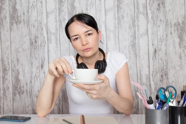 Jonge dame in wit overhemd koffie drinken luisteren naar muziek in zwarte koptelefoon notities op grijze muur opschrijven Gratis Foto