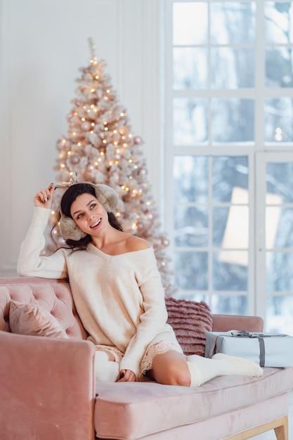 Jonge dame in witte jurk op de bank in de kersttijd Gratis Foto