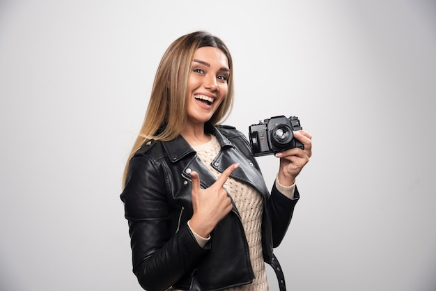 Jonge dame in zwart leren jasje fotograferen met camera op een positieve en glimlachende manier Gratis Foto