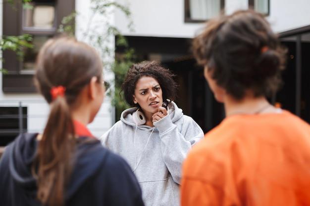 Jonge dame met donker krullend haar in koptelefoon staan en bedachtzaam kijken naar haar vriend terwijl ze tijd doorbrengt met studenten op de binnenplaats van de universiteit Premium Foto