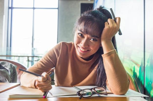Jonge dame met pennen aan tafel Gratis Foto