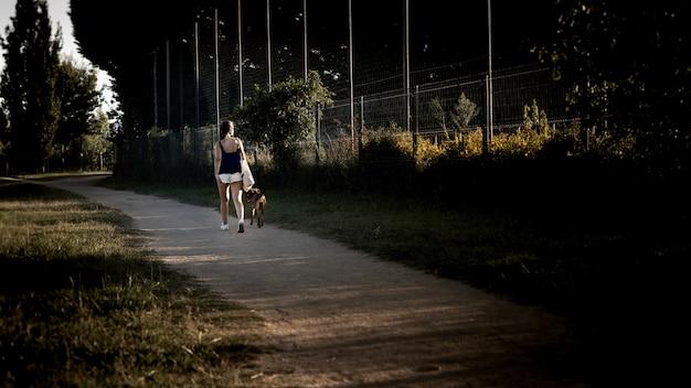 Jonge dame wandelen in het park langs het traject met haar hond op een mooie avond Gratis Foto