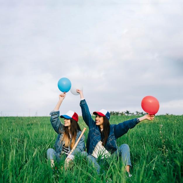 Jonge dames met plezier in de zomer veld met verschillende kleuren ballen Gratis Foto