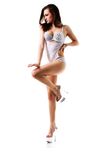 Jonge dansende slanke mooie brunette vrouw in sexy wit kostuum en hoge hakken schoenen geïsoleerd op witte achtergrond Premium Foto