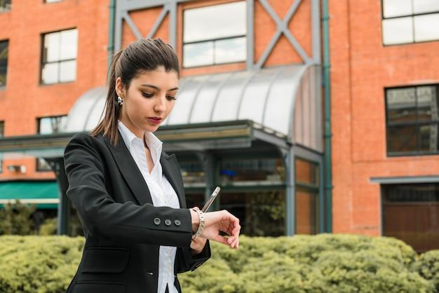 Jonge de celtelefoon van de onderneemsterholding die ter plaatse de tijd op polshorloge controleert Gratis Foto