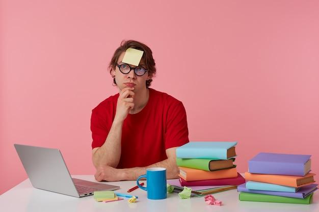 Jonge denkende man met bril draagt in rood t-shirt, met een sticker op zijn voorhoofd, zit bij de tafel en werkt met notitieboekje en boeken, kijkt omhoog en raakt kin, geïsoleerd op roze achtergrond. Gratis Foto