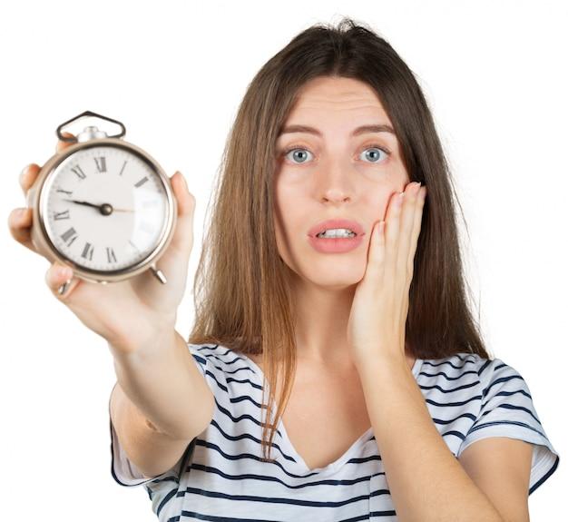 Jonge die vrouw met wekker op wit, het concept van het tijdbeheer wordt geïsoleerd Premium Foto