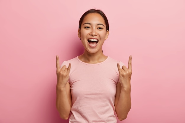 Jonge dolblij brunette vrouw met aziatische uitstraling, poseert met opgeheven armen hoorns en maakt rock gebaar, vrolijk en sartisfied, roept vrolijk, draagt casual roze t-shirt, poseert in Gratis Foto