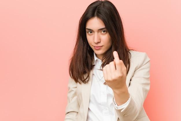 Jonge donkerbruine bedrijfsvrouw die tegen pink met vinger op u richt alsof uitnodigend dichter komt. Premium Foto