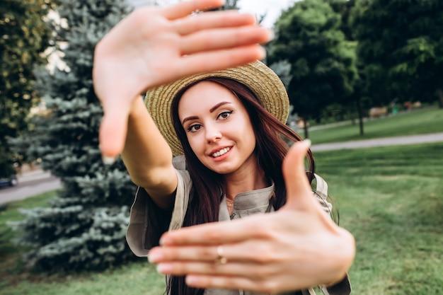 Jonge donkerbruine hipstervrouw die een selfie nemen, die tong, grappig gezicht tonen die in openlucht stellen. close-up portret van een meisje in een stijlvolle zomer hoed in een park. Premium Foto